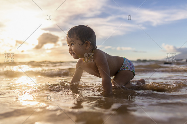 Baby girl crawling in ocean at sunset