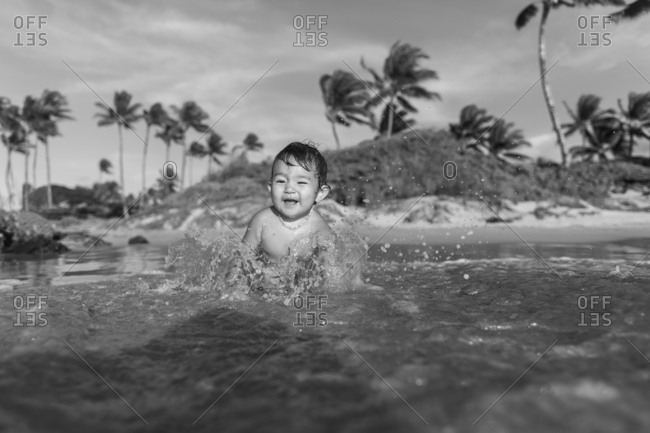 Baby splashing in water at the beach