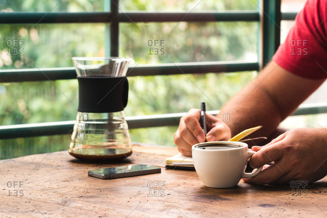 Man taking notes in a cafe