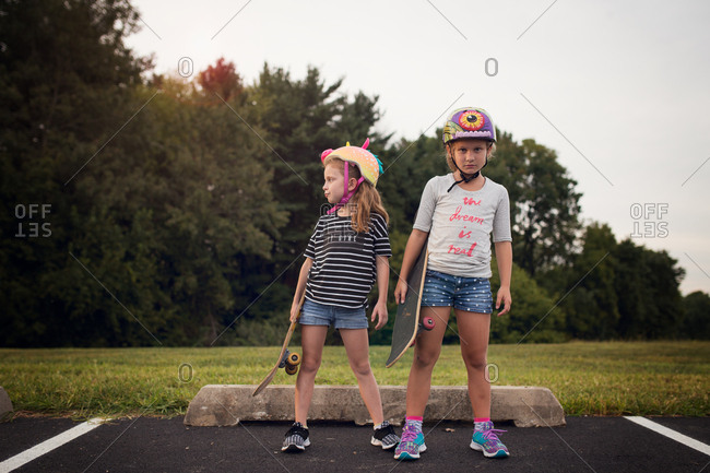 Two girls with skateboards one looking at camera