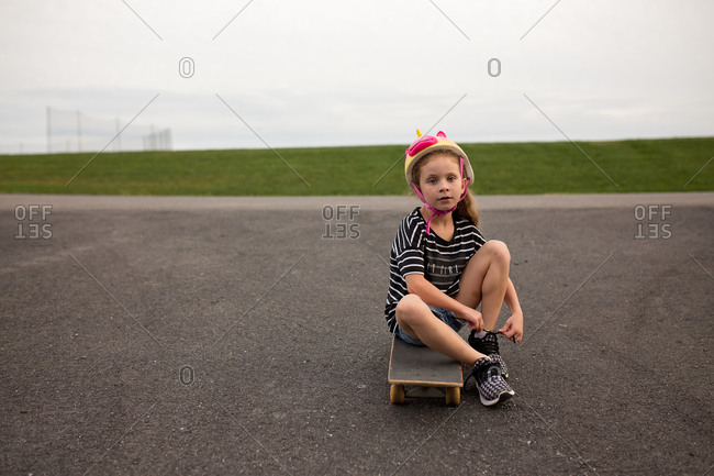 One girl sitting on a skateboard tying her shoe