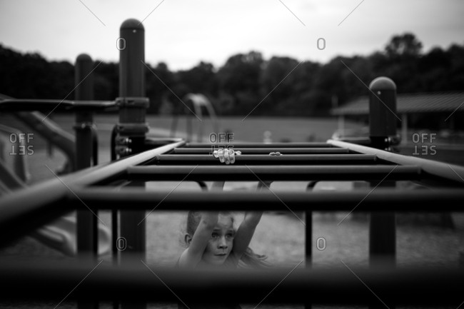Tip of fingers on monkey bars in black and white