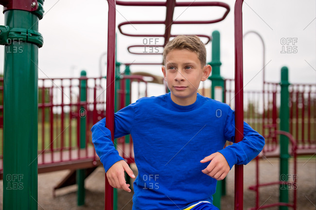 Boy sitting on jungle gym
