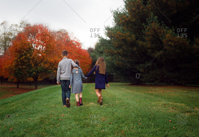 Siblings walking together holding hands with colorful trees in background