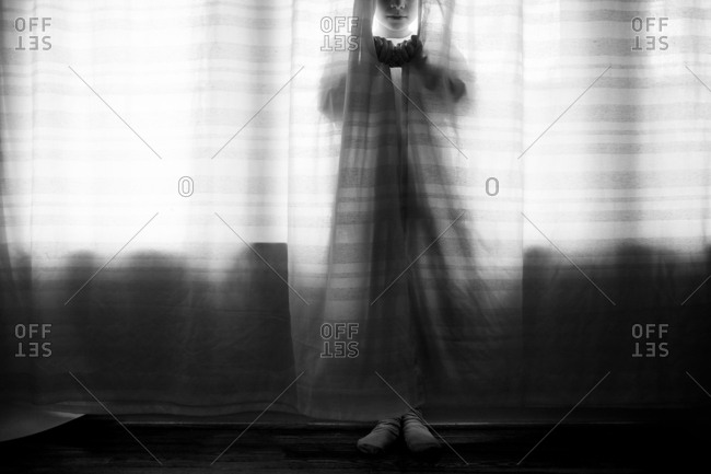 Black and white of girl in the curtains