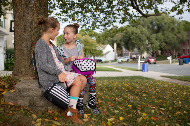 Girls talking under a tree waiting on the bus for school