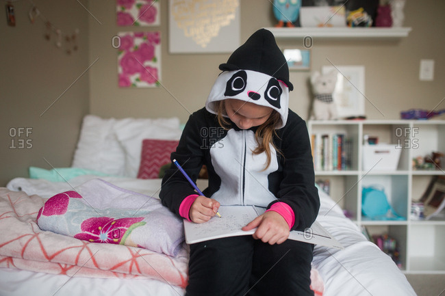 Girl in panda pajamas writing in book