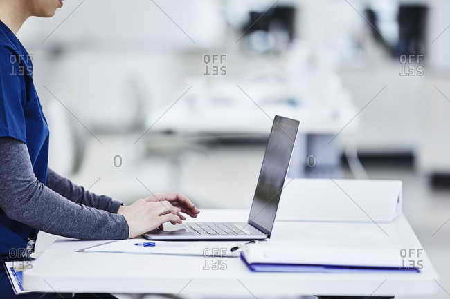 Nurse using laptop at desk in medical lab
