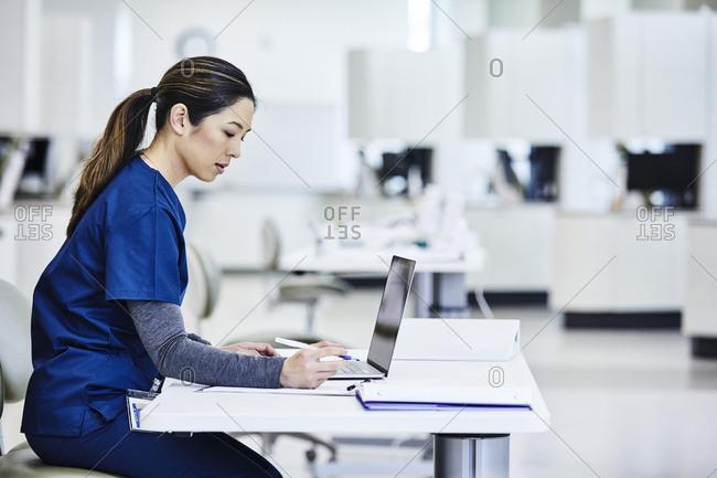 Nurse using laptop in medical lab