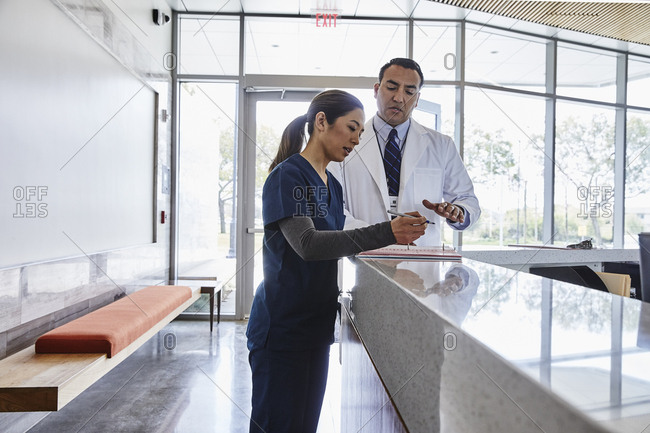 Male doctor talking to nurse in reception area of medical office
