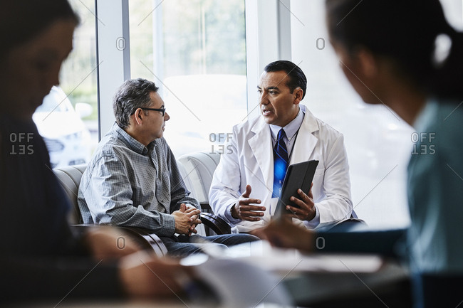 Male doctor discussing with patient at lobby of medical clinic