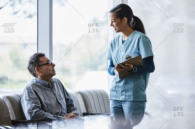Smiling female nurse discussing with senior male patient sitting at lobby in hospital