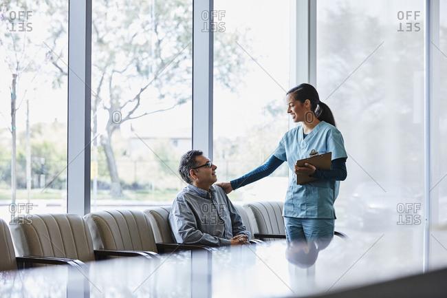 Happy female nurse comforting senior man  sitting in lobby at hospital