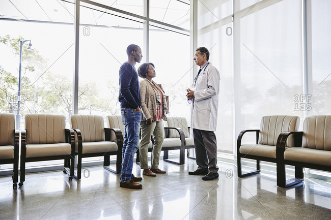 Doctor discussing with patients in waiting room at medical clinic