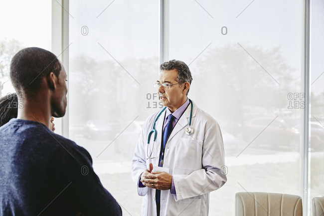 Confident male doctor consulting with patients in hospital lobby