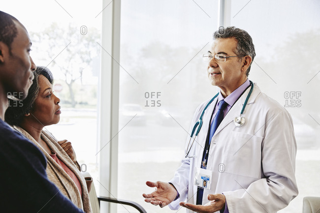 Doctor speaking to mother and son in waiting room