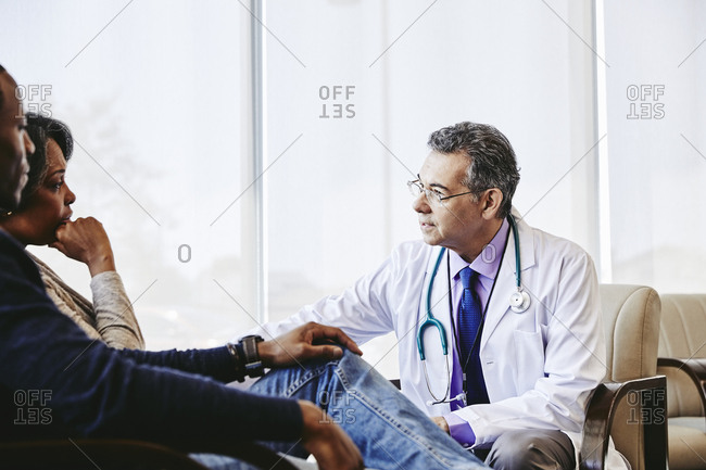 Mature male doctor discussing with family while sitting in hospital lobby