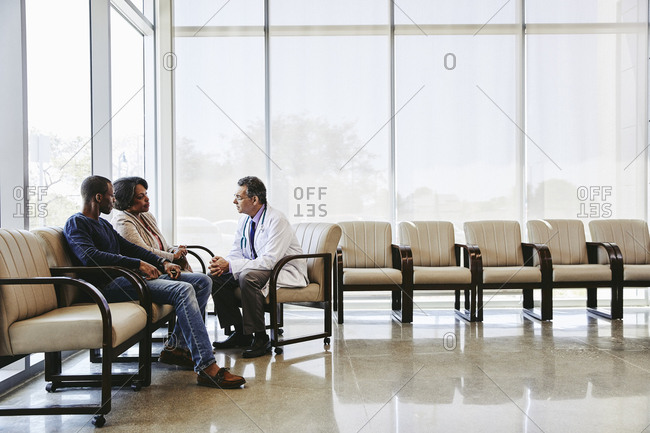 Doctor discussing with family while sitting hospital waiting room