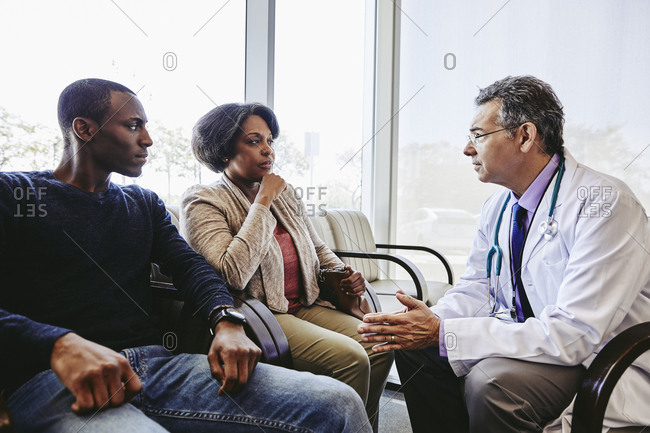 Confident doctor with hands clasped talking to family in hospital lobby