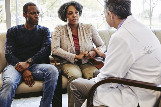 Male doctor comforting mature woman sitting with son in hospital waiting room