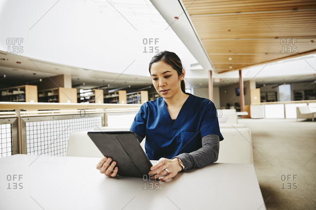Mid adult female medical student using digital tablet at table in library