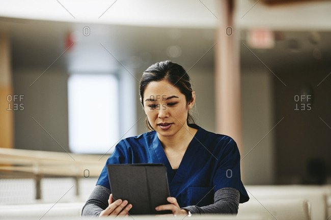 Mid adult female medical student using digital tablet at table in hospital library