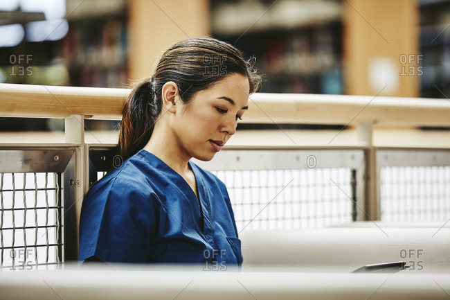 Female medical student looking at notes on digital tablet