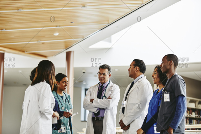 Male and female medical professionals discussing while standing in hospital
