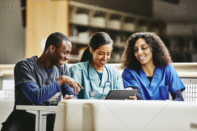 Medical students using digital tablet in library at hospital