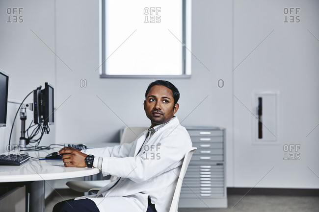 Side view of thoughtful male doctor sitting at computer desk in hospital