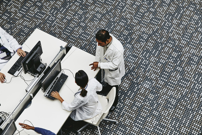 High angle view of male and female doctors discussing at computer desks medical office