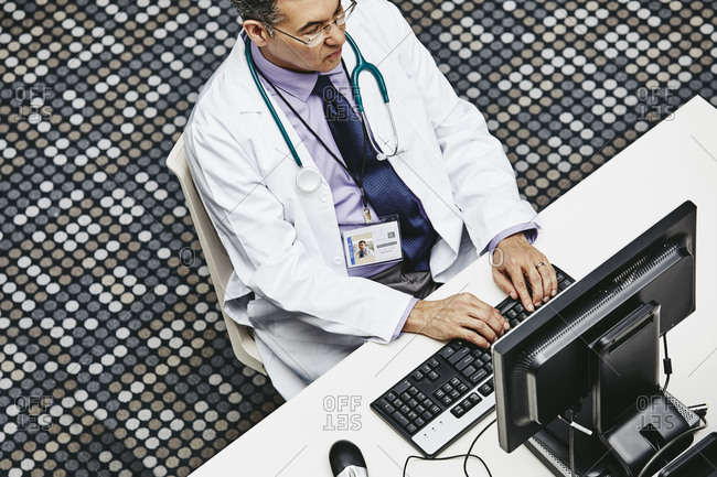 High angle view of male doctor using computer at desk in hospital