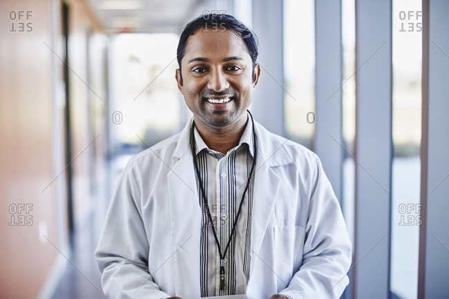 Portrait of confident mid adult male doctor standing at corridor in hospital