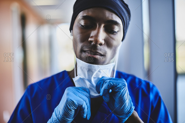 Depressed young male surgeon removing mask at hospital