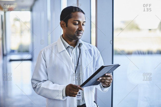 Mid adult male doctor using digital tablet while standing at corridor at hospital