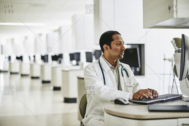 Mid adult male doctor using computer in dental clinic