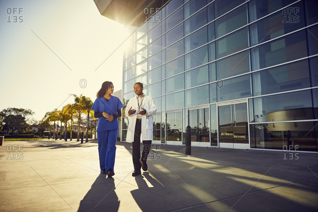 Full length of doctor talking to nurse while walking outside hospital building during sunny day