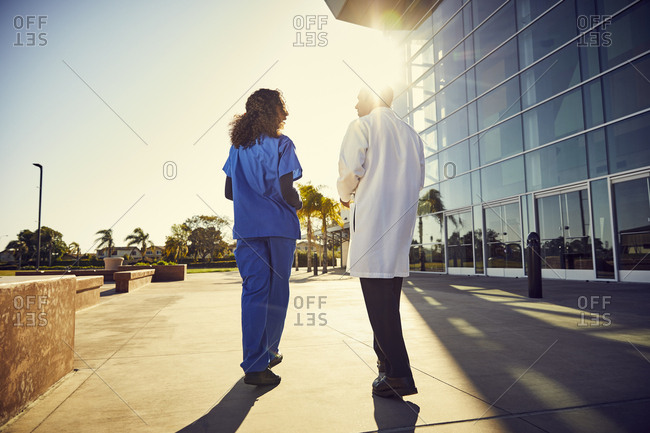 Full length rear view of doctor and nurse communicating outside hospital