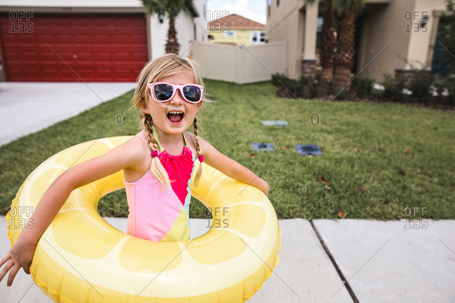 Happy girl in swimsuit wearing a yellow pool float and sunglasses