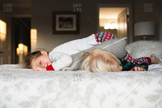 Little girl lays on top of her brother after a pillow fight in bed