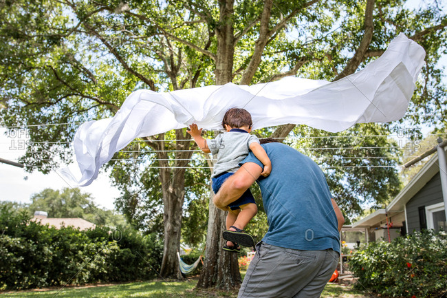 Father and son running through sheets drying on a clothesline