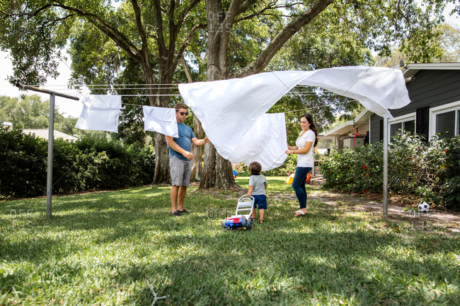 Family of three hanging laundry to dry outside