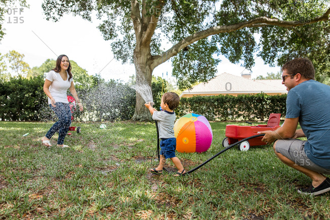 Little boy chases mom with garden hose