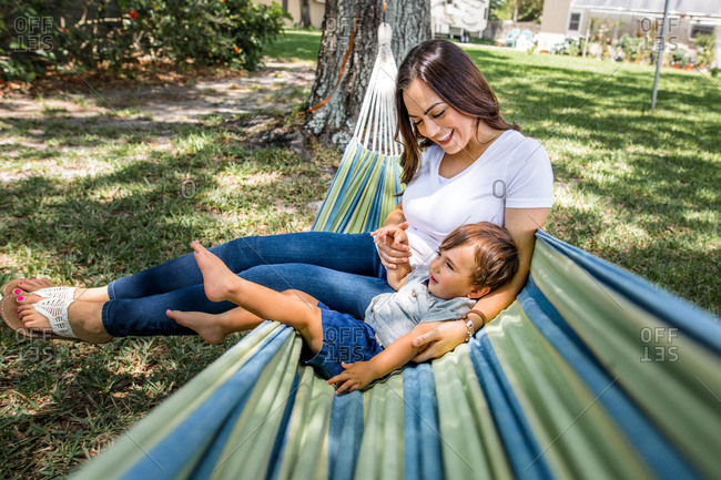 Son lays with mom in hammock outside