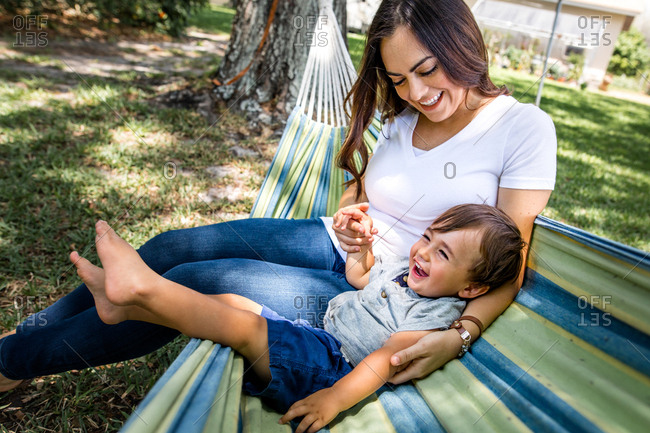 Mom son lay in hammock outside while smiling