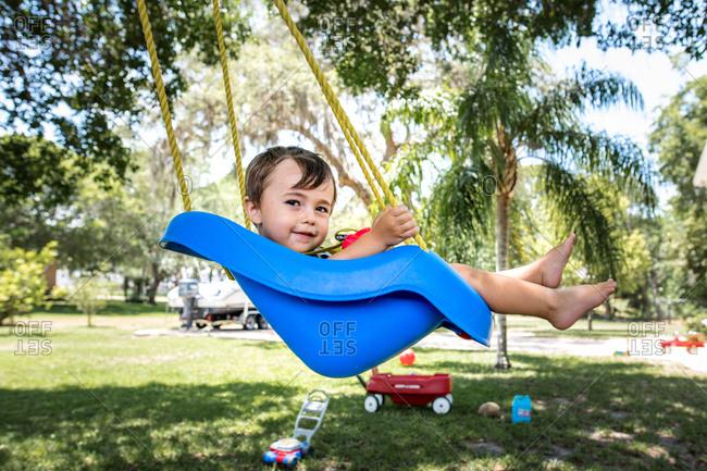 Little boy smiles at camera as he swings in tree swing