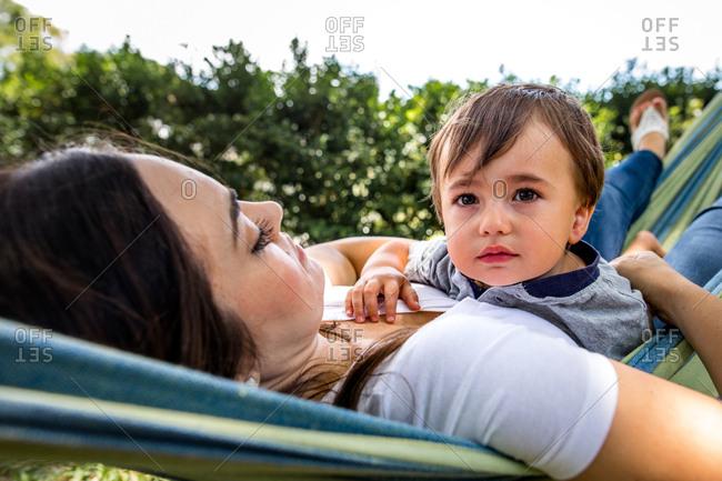 Little boy lays with mom in hammock outside