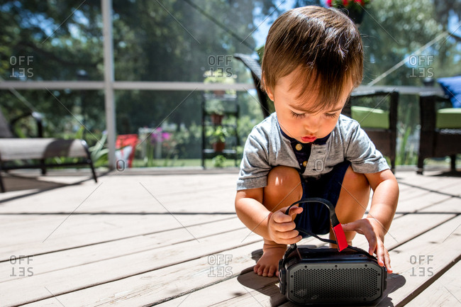 Little boy plays with audio speaker on back patio