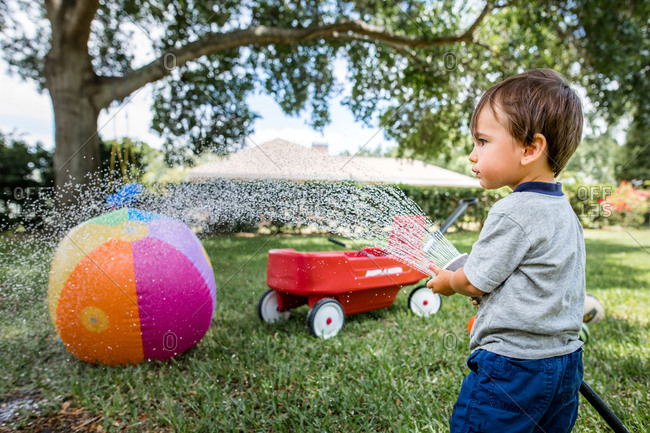 Little boy plays with garden hose in backyard