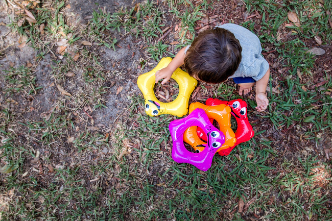 Little boy plays with colorful plastic toys in backyard shot from above
